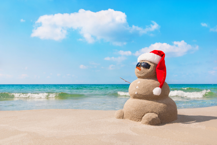 Christmas snowman in santa hat at sandy beach
