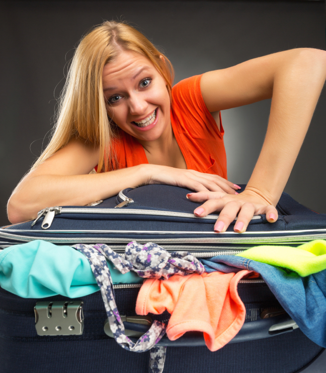 Woman struggles to shut a full suitcase