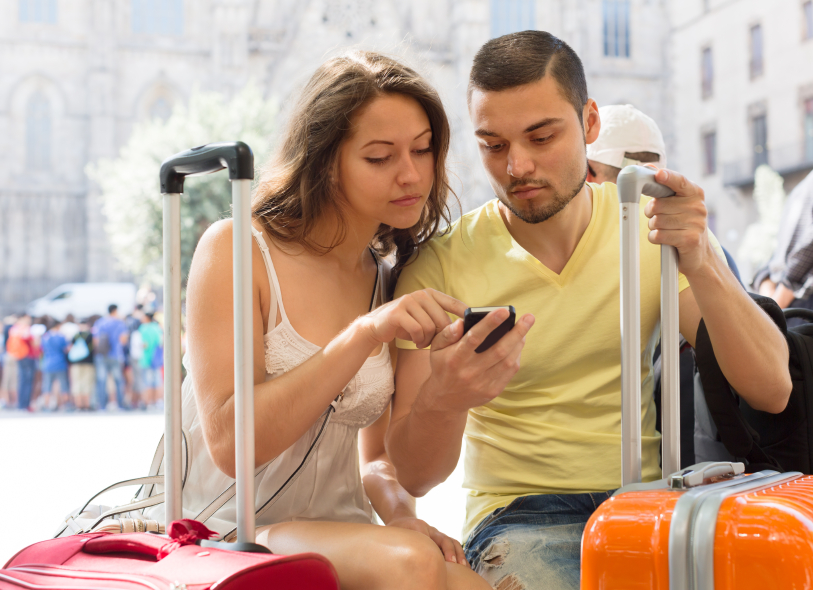 Happy travellers using mobile navigating system