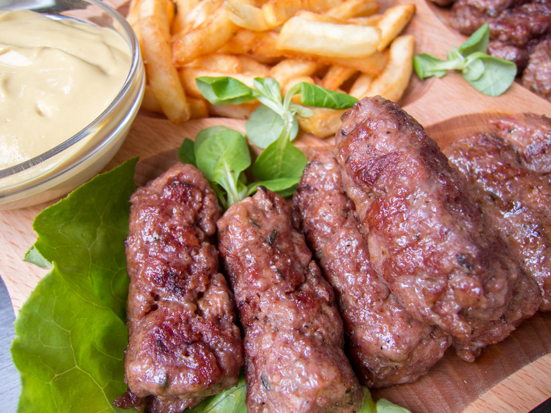 romanian traditional food meat rolls mici with fries and mustard