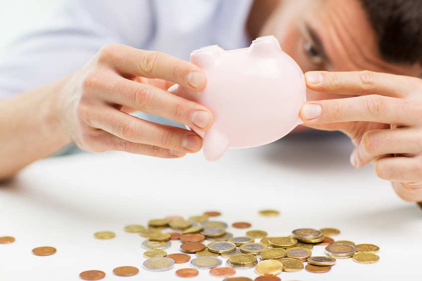 close up of man pouring coins from piggy bank