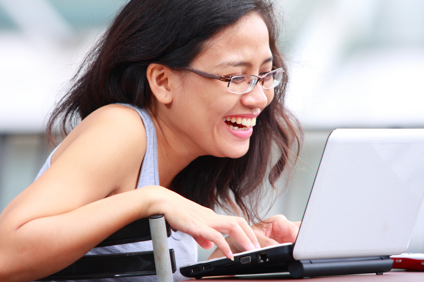 happy young asian woman using laptop